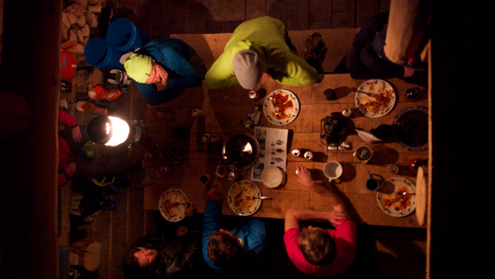 Discussing a day's tour over boxed wine and bourbon at Beartooth Powder Guides' Woody Creek Cabin. Beartooth Mountains, Mont. [Photo] Tyler Cohen