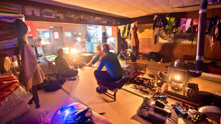 Nightlife in Shokatan Hut, featuring cold sake and fried gyoza—Japanese dumplings—after a day skiing thousand-foot descents among silver birches. [Photo] Freya Fennwood