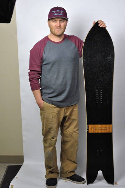 Mikey Franco standing with one of his custom boards. [Photo] Patrick Shehan