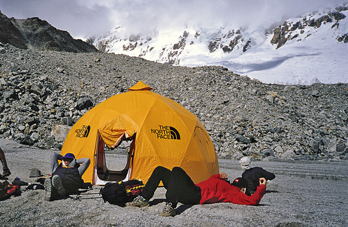 Mark Holbrook (left) and Hans Saari dozing at advanced base camp. Lowe and Bridges were killed in the large, open glaciers above, and the avalanche came down from the peaks in the clouds. [Photo] Andrew McLean