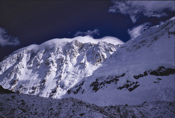 The southwest face of Shishapangma. The summit has a lenticular cloud on it, and the slopes that avalanched are the ones in the shade off to the right with the cliff bands. McLean was standing on top of the moraine looking down and into the hidden valley on the other side. [Photo] Andrew McLean