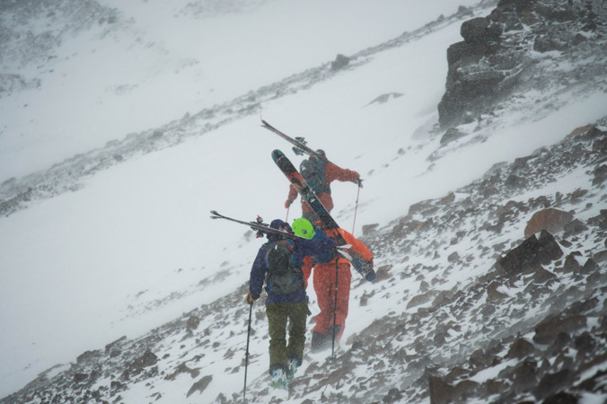 Lucy Higgins, Curtis Berklund and Austin Johnson shoulder thier skis for the wind buffeted scree fields on the way to La Chiminea Couloir in TK. [Photo] Jacob O'Connor