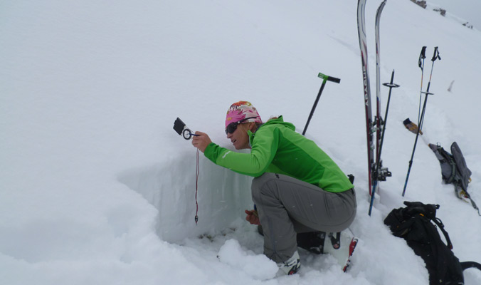 Sarah Carpenter measures slope angle. [Photo] Courtesy American Avalanche INstitute