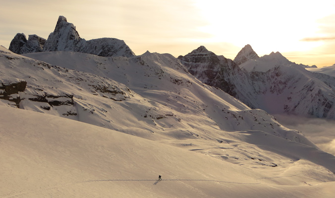 A skier skirts Mt. Tupper, Mt. MacDonald and Mt. Sir Donald in Rogers Pass. [Photo] P. Schaedler for Parks Canada
